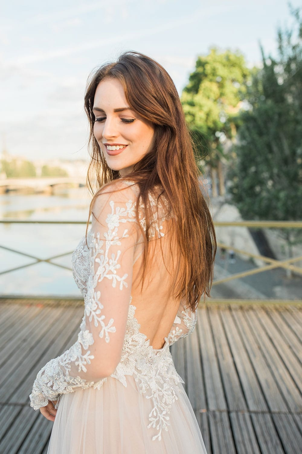 Model wearing Vinka Design Suri Wedding Dress, a Backless Silver Tulle and Lace Gown with Long Sleeves on a boardwalk in Paris
