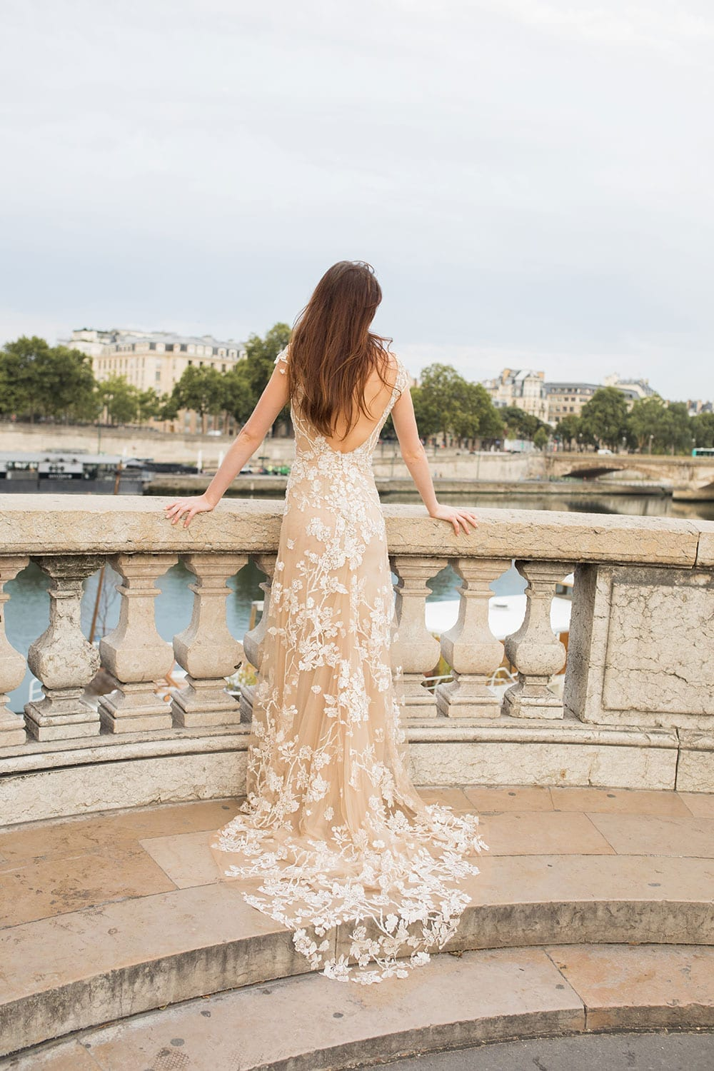 Model wearing Vinka Design Vianna Wedding Dress, a Low Back Beaded Wedding Gown with train looking out from a promenade in Paris