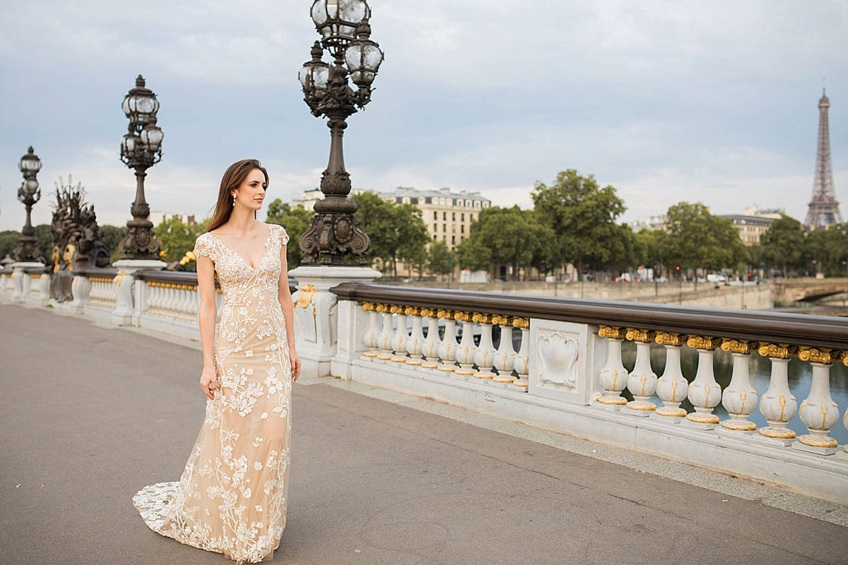 Model wearing Vinka Design Vianna Wedding Dress, a Low Back Beaded Wedding Gown with train walking along a promenade in Paris