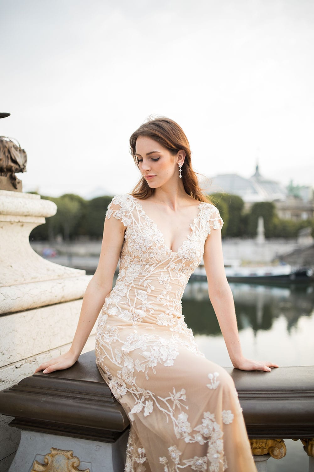 Model wearing Vinka Design Vianna Wedding Dress, a Low Back Beaded Wedding Gown with train sitting on the wall of a promenade in Paris