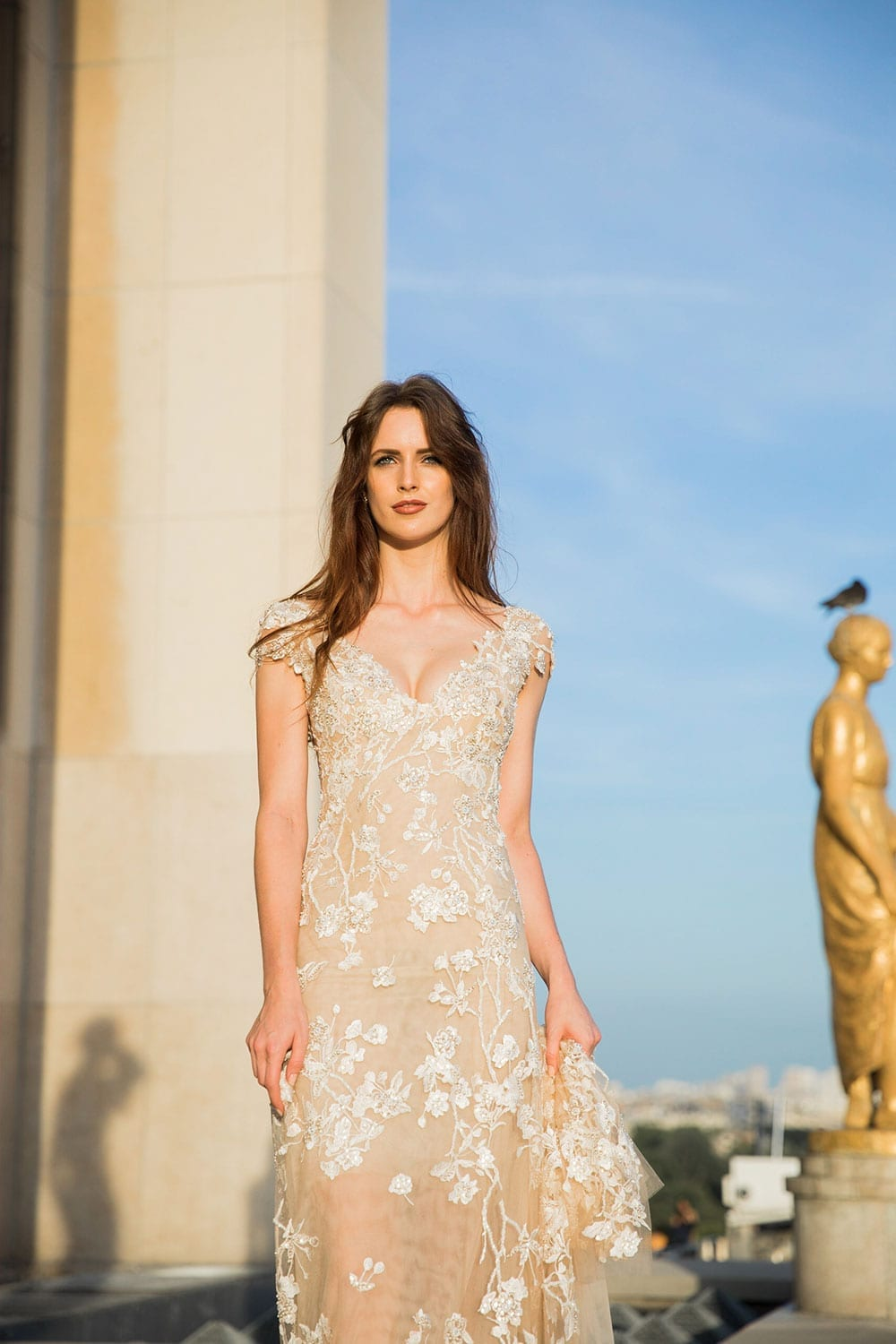 Model wearing Vinka Design Vianna Wedding Dress, a Low Back Beaded Wedding Gown next to monument in Paris