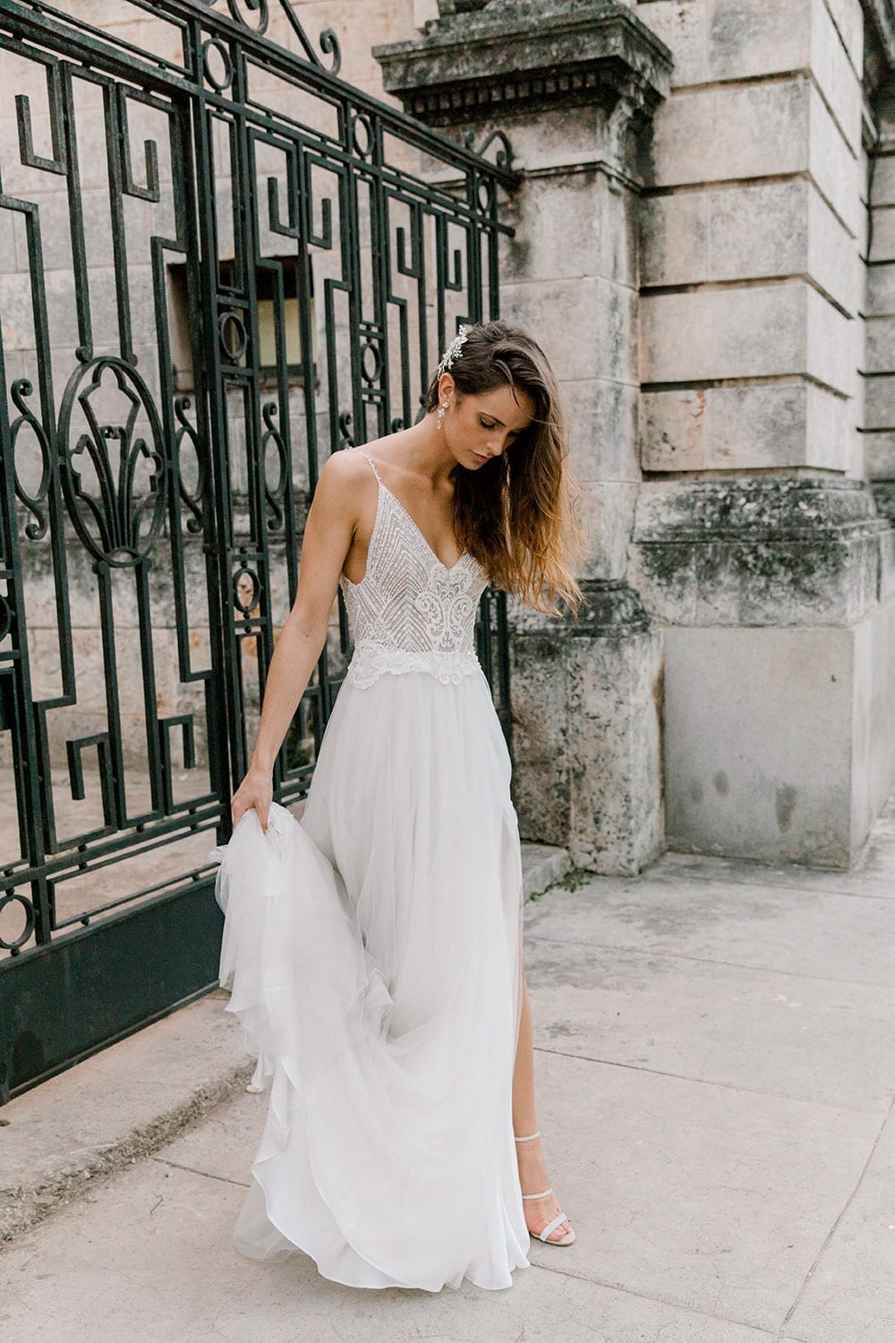 Model wearing Vinka Design Lucia Wedding Dress with Fitted Beaded Bodice, Tulle Skirt and Split in front of old iron gate in Havana