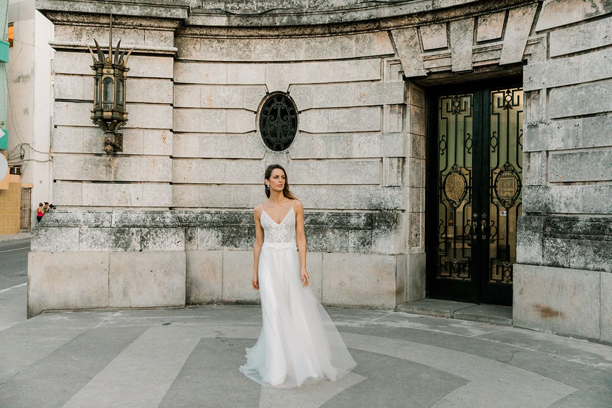 Model wearing Vinka Design Lucia Wedding Dress with Fitted Beaded Bodice, Tulle Skirt and Split in front of old building in Havana
