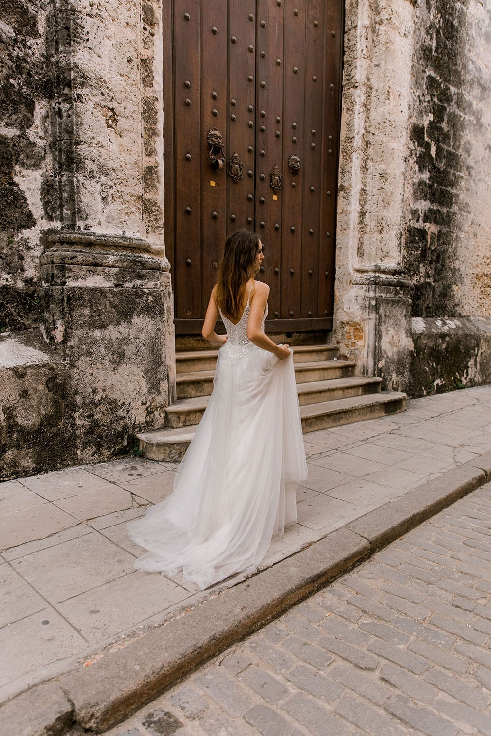Model wearing Vinka Design Lucia Wedding Dress with Fitted Beaded Bodice, Tulle Skirt and Split walking in front of old building in Havana