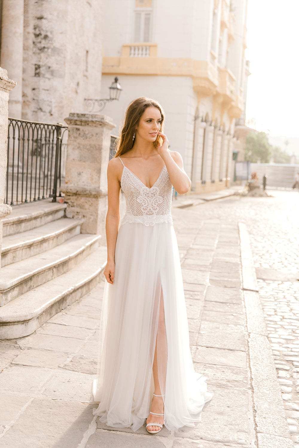 Model wearing Vinka Design Lucia Wedding Dress with Fitted Beaded Bodice, Tulle Skirt and Split walking in front of old church in Havana