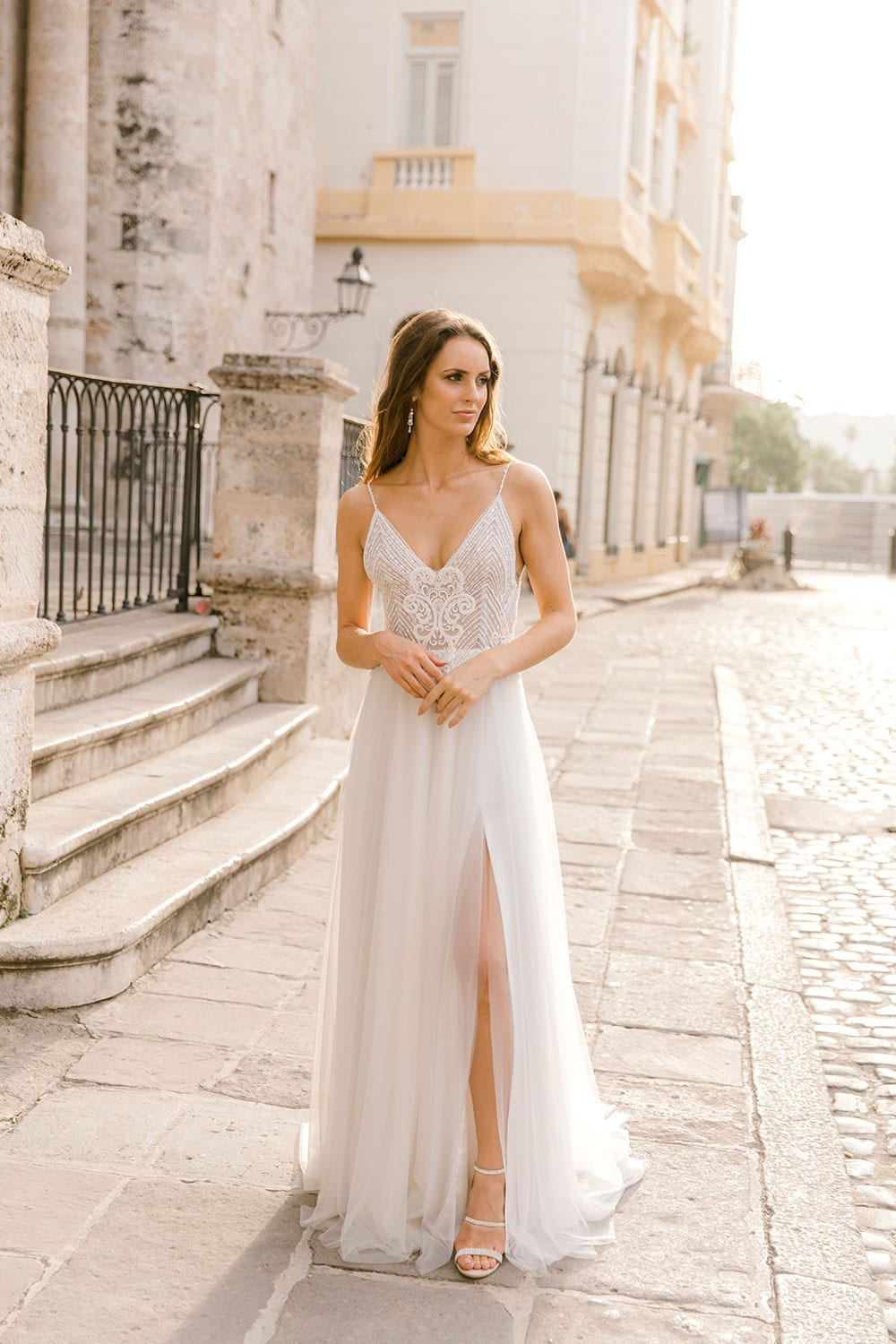 Model wearing Vinka Design Lucia Wedding Dress with Fitted Beaded Bodice, Tulle Skirt and Split walking in front of old church in plaza in Havana