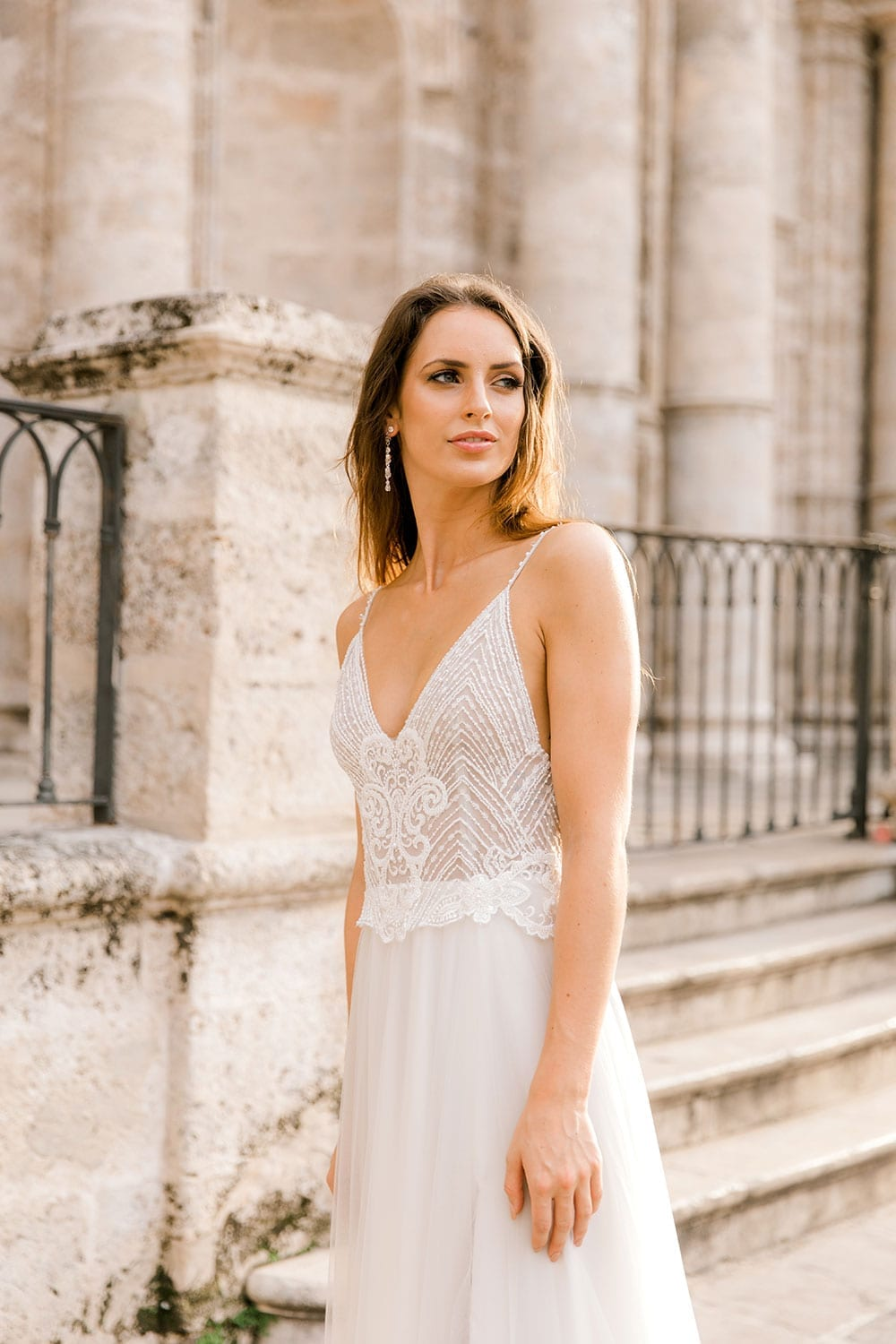 Model wearing Vinka Design Lucia Wedding Dress with Fitted Beaded Bodice, Tulle Skirt and Split walking in front of old church steps in Havana