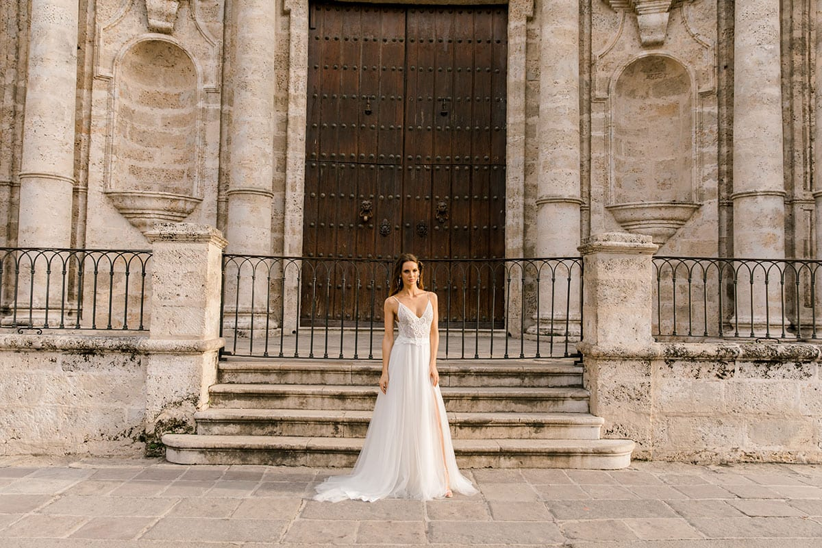 Model wearing Vinka Design Lucia Wedding Dress with Fitted Beaded Bodice, Tulle Skirt and Split in front of old church steps in Havana