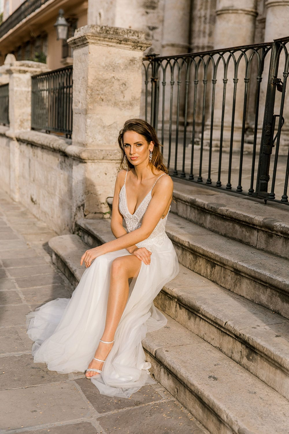 Model wearing Vinka Design Lucia Wedding Dress with Fitted Beaded Bodice, Tulle Skirt and Split in front of old church sitting on steps in Havana