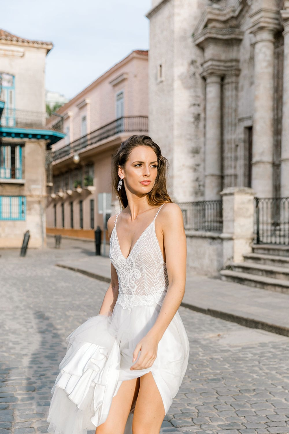 Model wearing Vinka Design Lucia Wedding Dress with Fitted Beaded Bodice, Tulle Skirt and Split in front of old church plaza in Havana