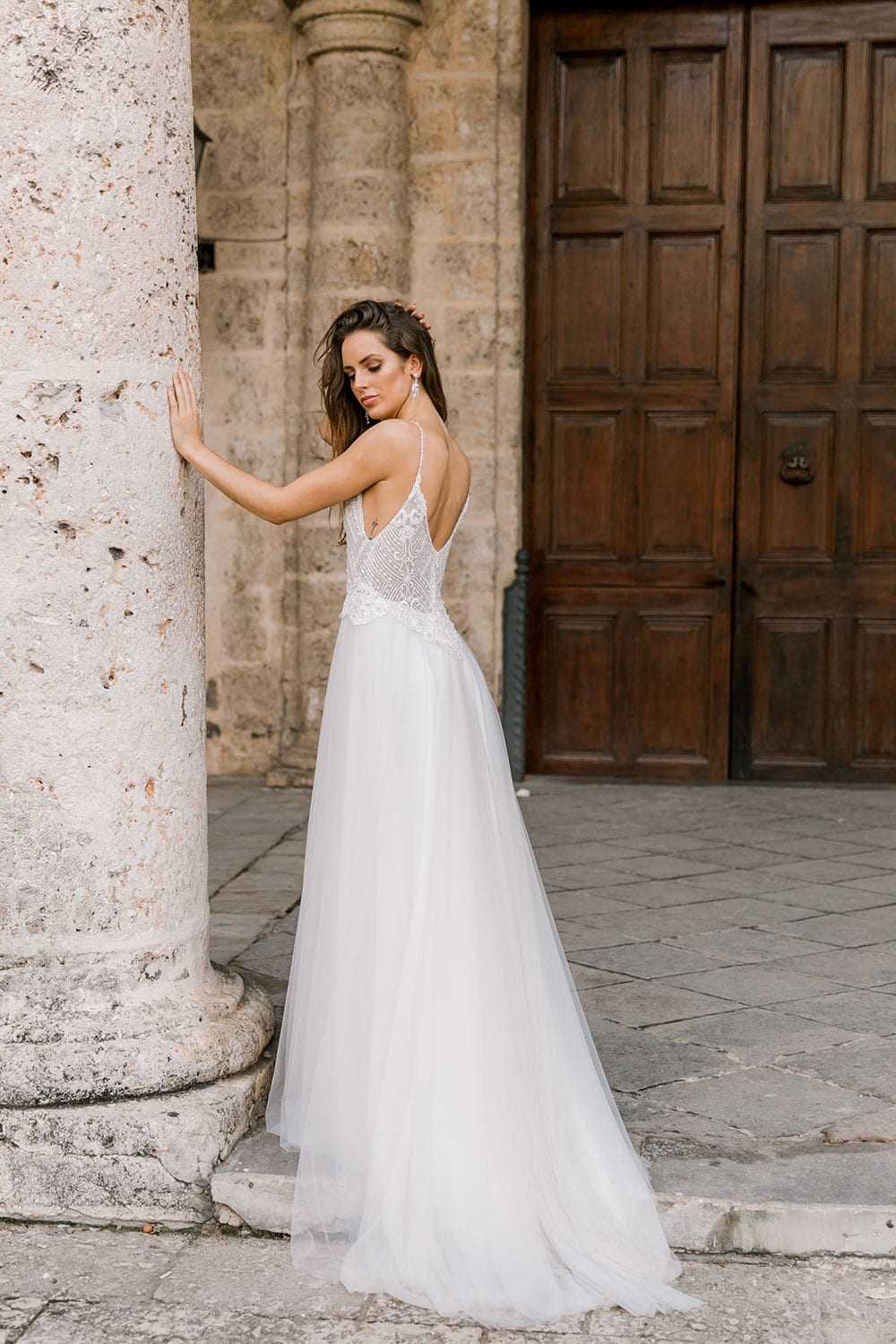 Model wearing Vinka Design Lucia Wedding Dress with Fitted Beaded Bodice, Tulle Skirt and Split in front of old church door in Havana