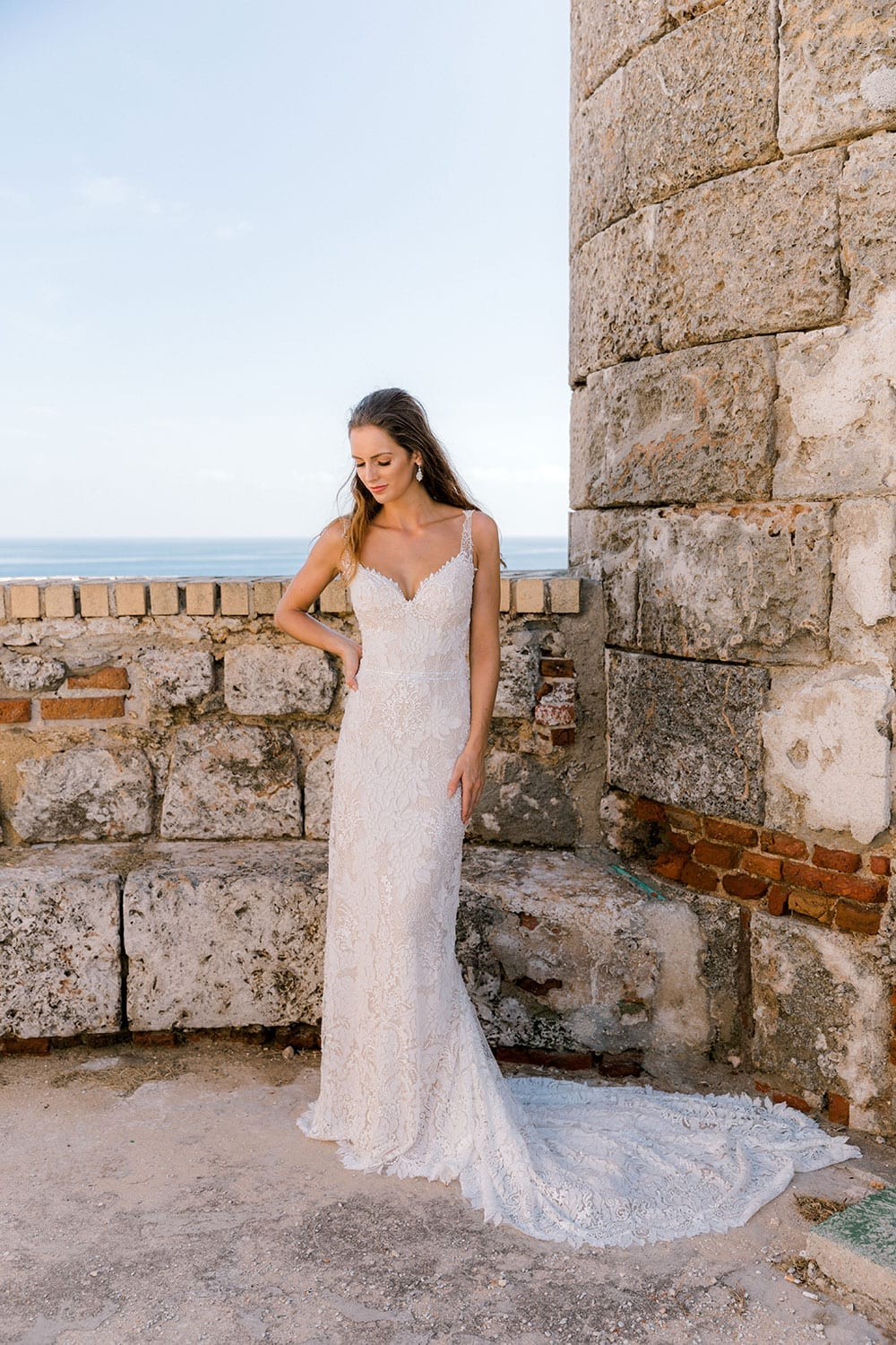 Model wearing Vinka Design Miriam Wedding Dress, a Beaded Lace Wedding Gown next to old stone wall in Cuba