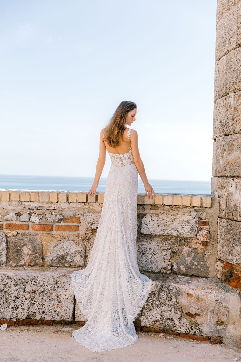 Model wearing Vinka Design Miriam Wedding Dress, a Beaded Lace Wedding Gown looking out across ocean in Cuba