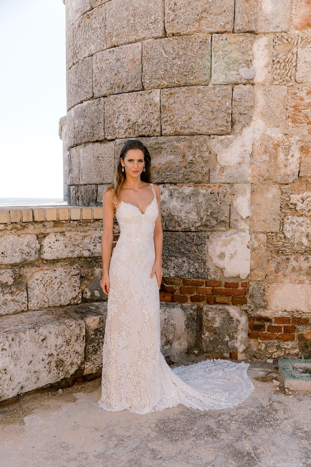 Model wearing Vinka Design Miriam Wedding Dress, a Beaded Lace Wedding Gown in front of old wall in Cuba