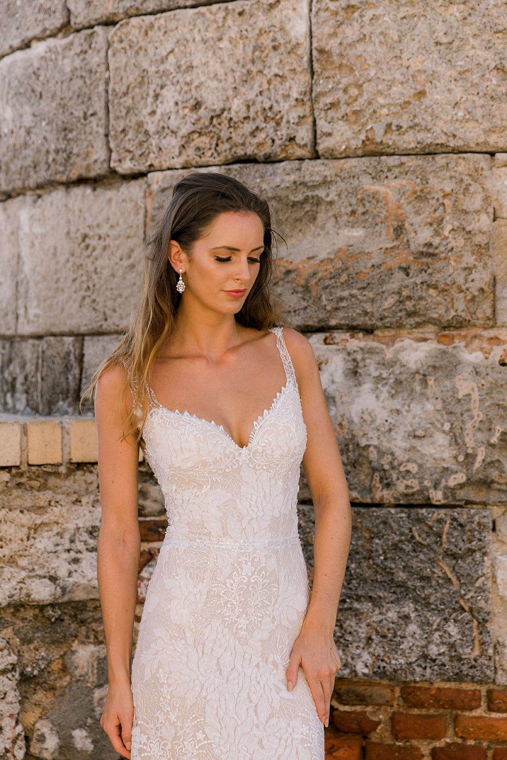Model wearing Vinka Design Miriam Wedding Dress, a Beaded Lace Wedding Gown in front of large stone wall in Cuba