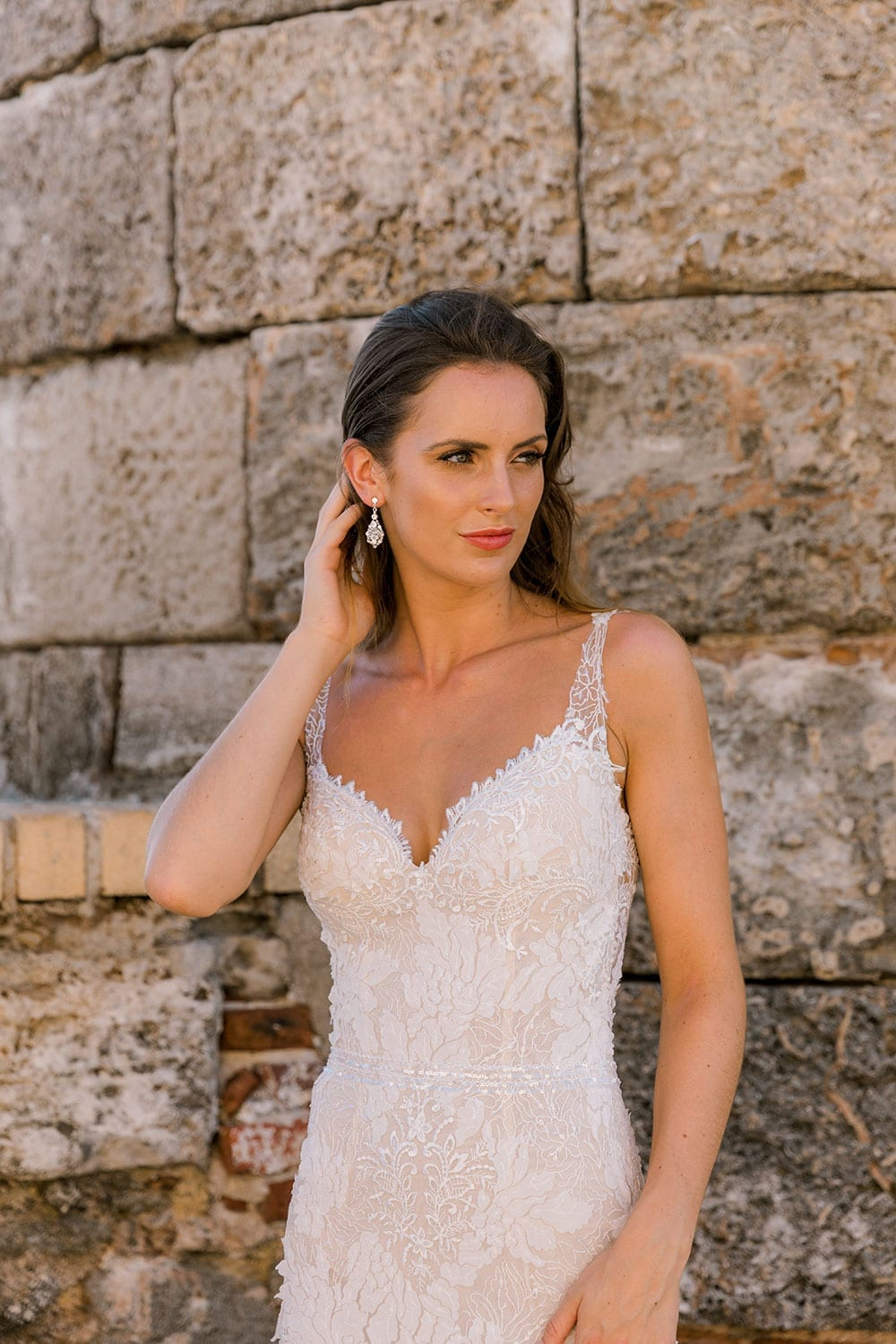 Model wearing Vinka Design Miriam Wedding Dress, a Beaded Lace Wedding Gown close up in front of old wall in Cuba
