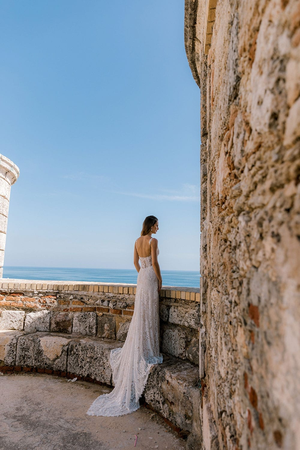 Model wearing Vinka Design Miriam Wedding Dress, a Beaded Lace Wedding Gown looking out to sea on an wall in Cuba