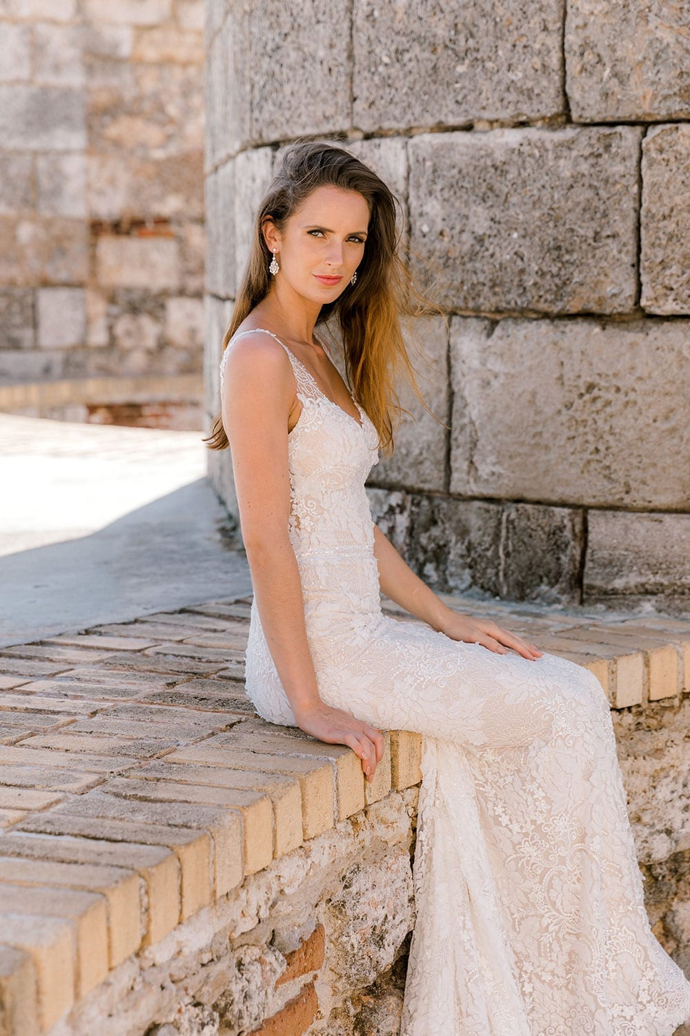 Model wearing Vinka Design Miriam Wedding Dress, a Beaded Lace Wedding Gown sitting on old wall in Cuba