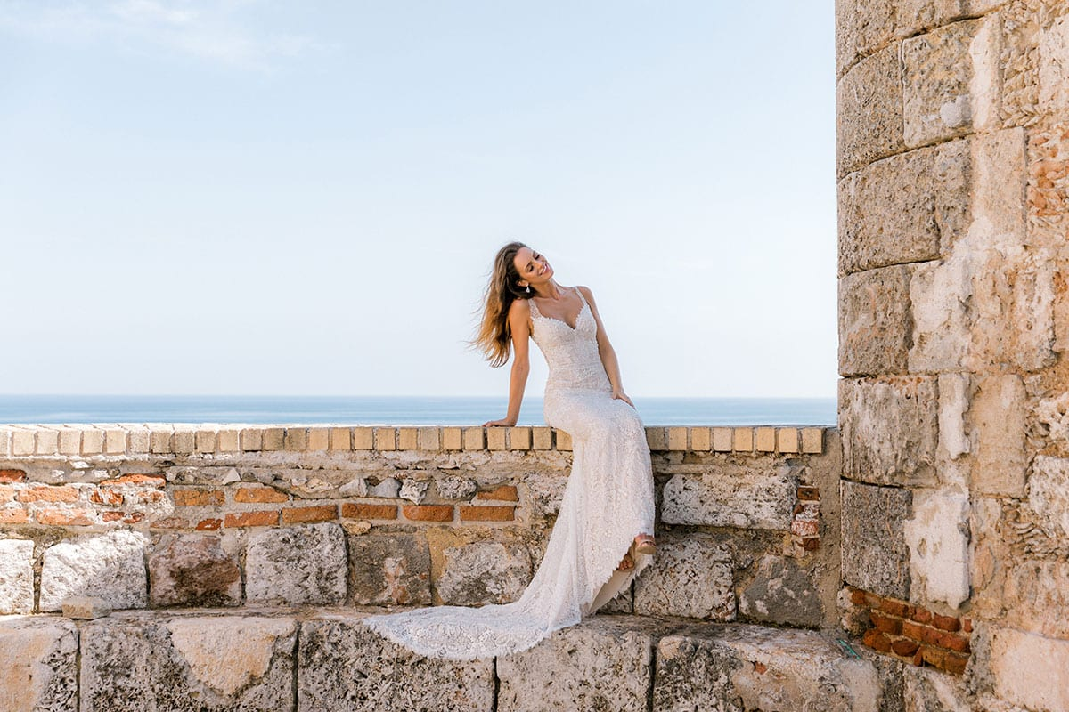 Model wearing Vinka Design Miriam Wedding Dress, a Beaded Lace Wedding Gown on old wall in Cuba
