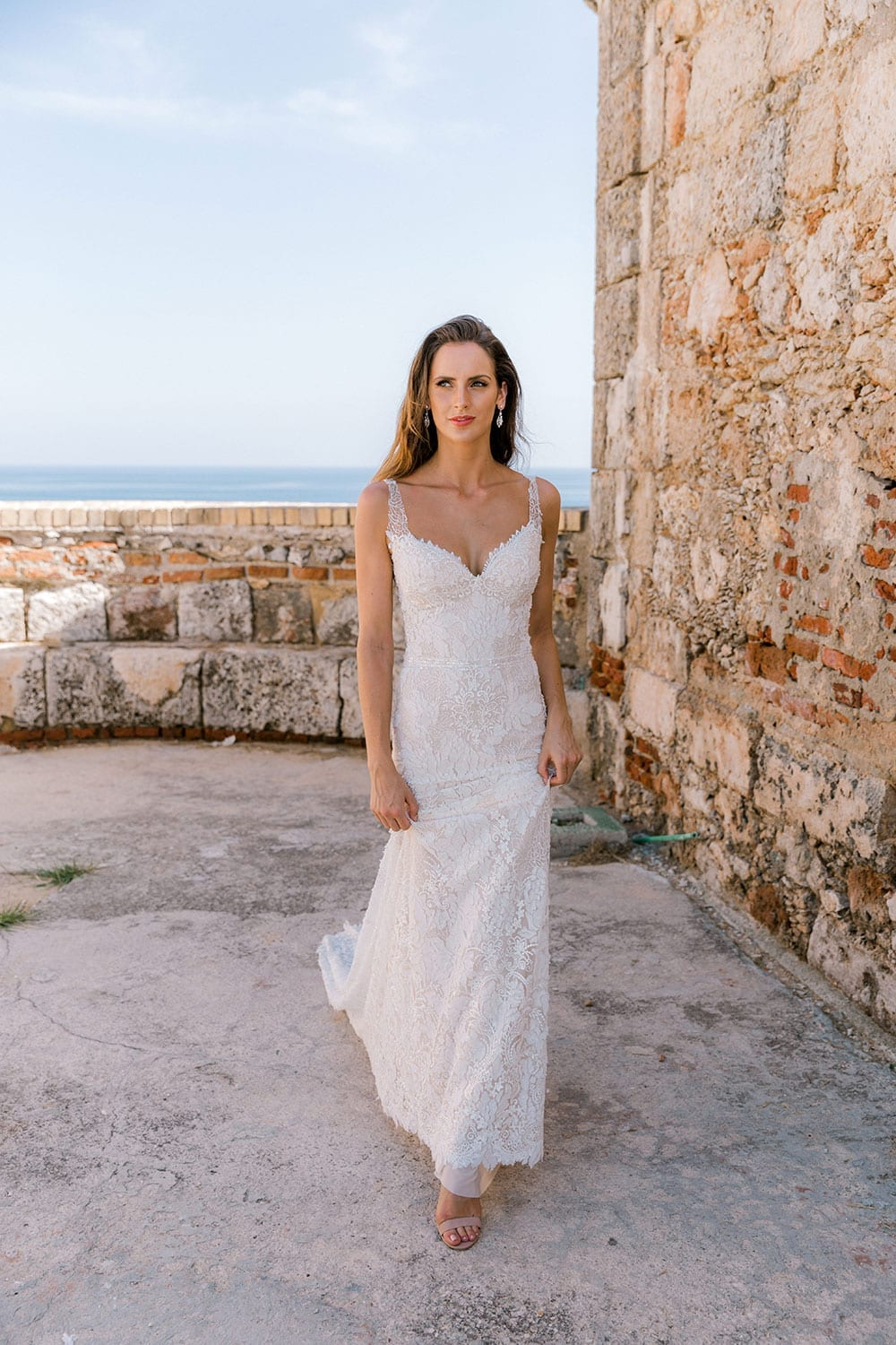 Model wearing Vinka Design Miriam Wedding Dress, a Beaded Lace Wedding Gown walking along old path in Cuba
