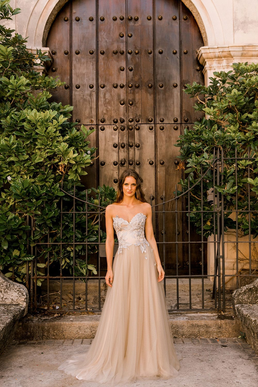 Model wearing Vinka Design Narnia Wedding Dress, a Strapless Tulle Gown with Silver Embroidered Lace Detail in front of a wooden doorway in Cuba