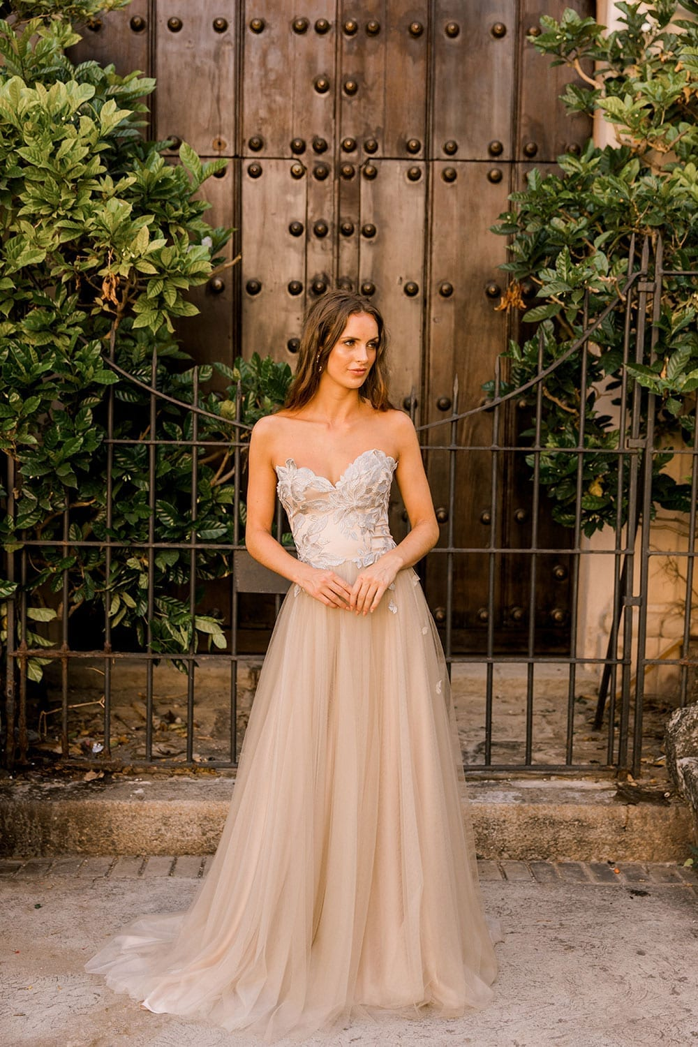 Model wearing Vinka Design Narnia Wedding Dress, a Strapless Tulle Gown with Silver Embroidered Lace Detail in front of a wooden doorway with hands clasped in Cuba