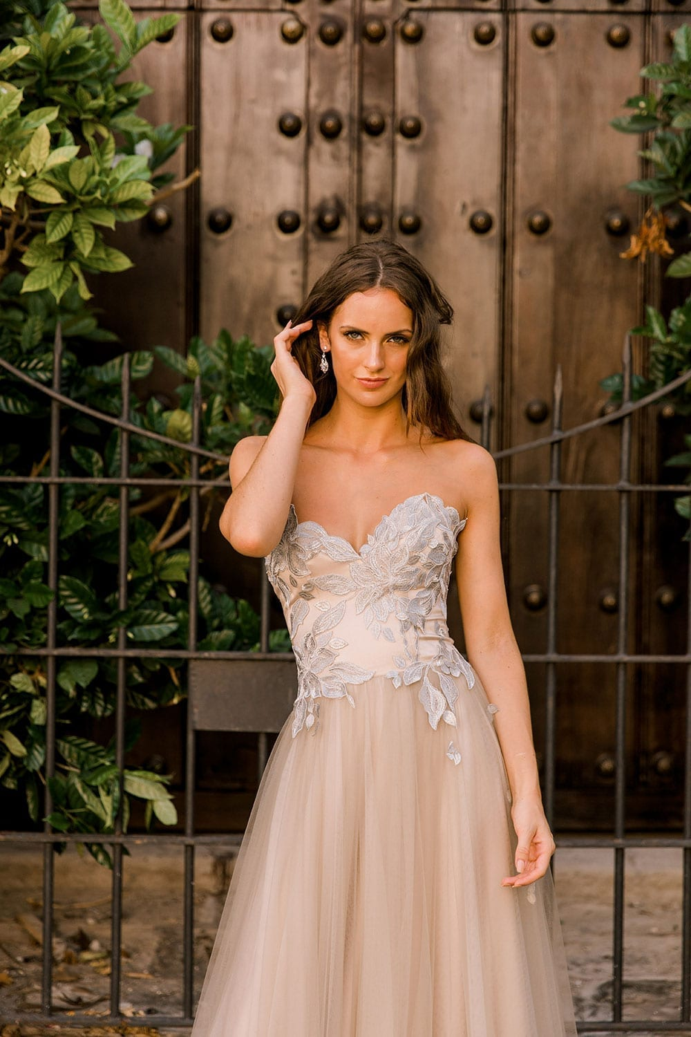 Model wearing Vinka Design Narnia Wedding Dress, a Strapless Tulle Gown with Silver Embroidered Lace Detail close up in front of a wooden doorway in Cuba