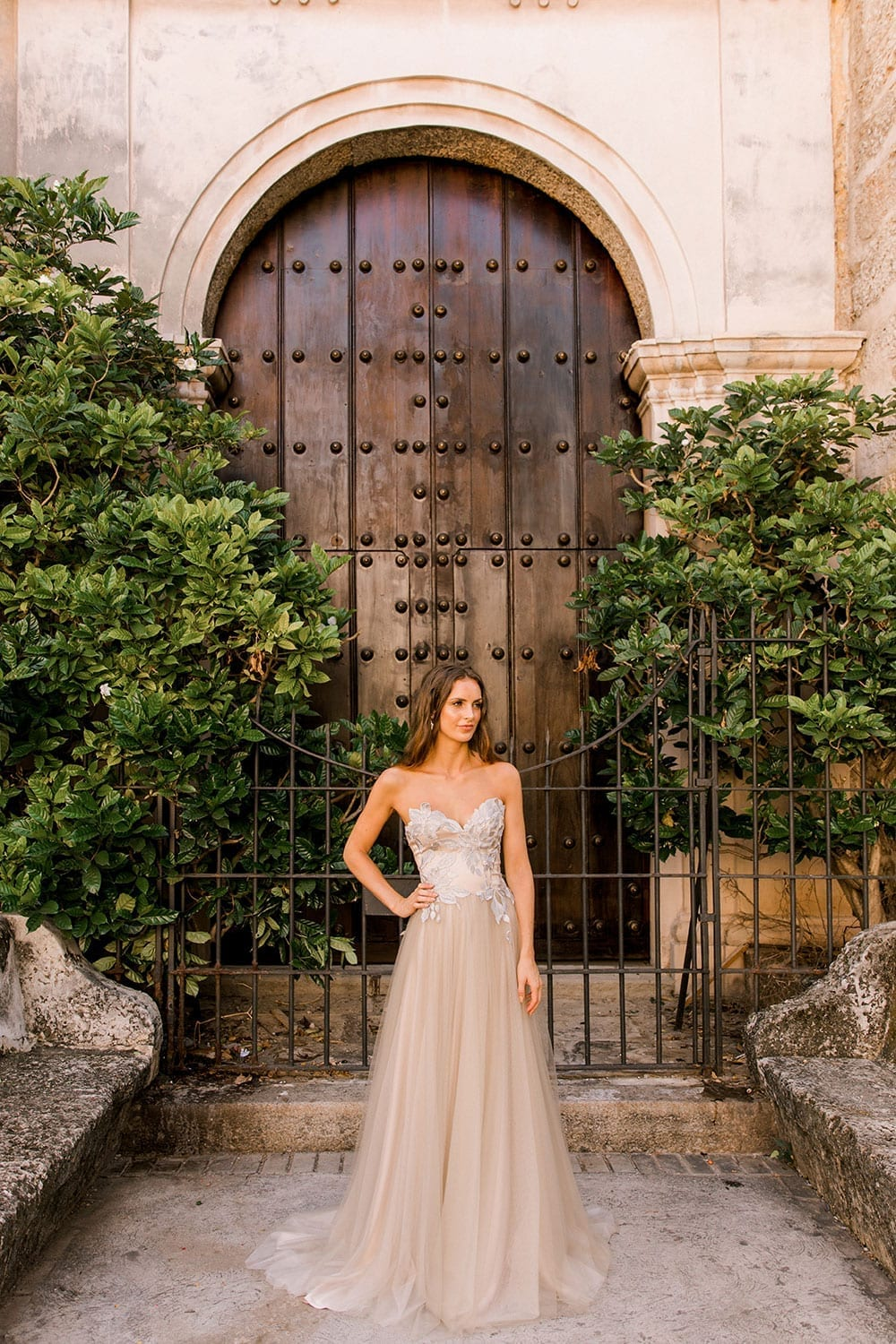 Model wearing Vinka Design Narnia Wedding Dress, a Strapless Tulle Gown with Silver Embroidered Lace Detail hand on hip in front of a wooden doorway with arch in Cuba