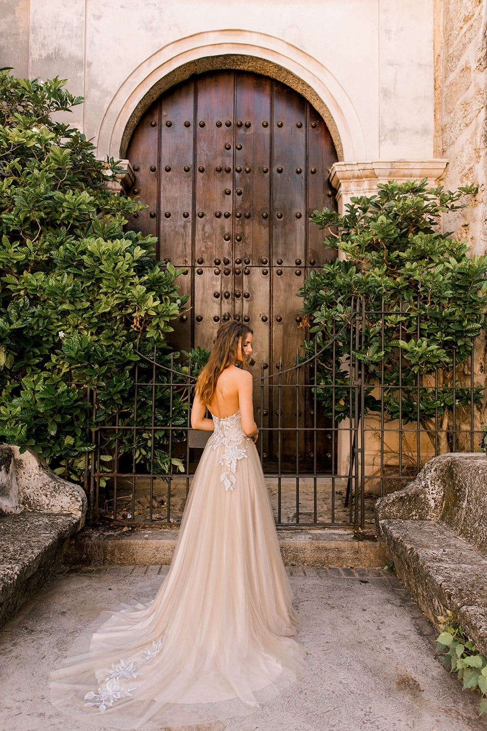 Model wearing Vinka Design Narnia Wedding Dress, a Strapless Tulle Gown with Silver Embroidered Lace Detail facing away in front of a wooden doorway with arch in Cuba