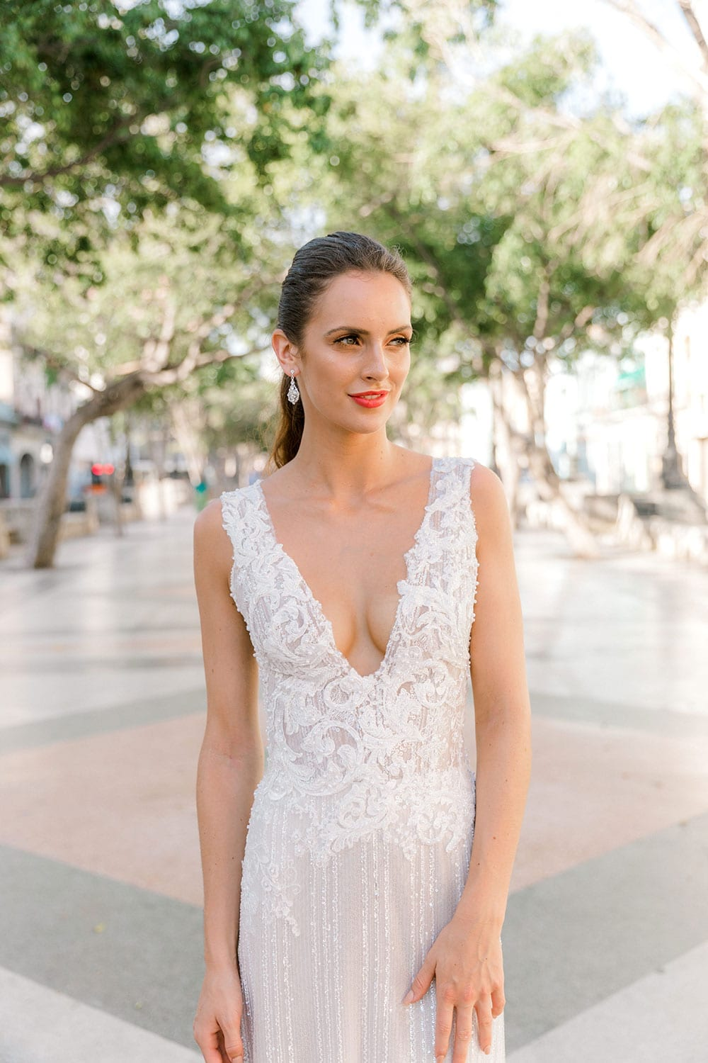 Model wearing Vinka Design Natalia Wedding Dress, a V-Neck Beaded Lace Wedding Gown in a Cuban plaza