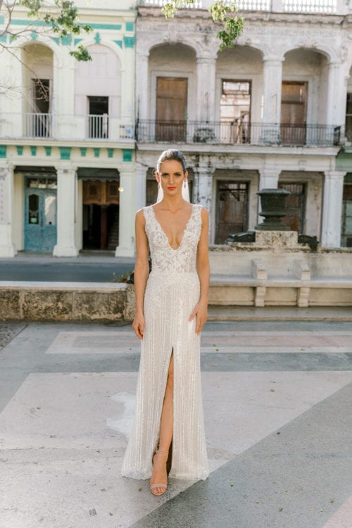 Model wearing Vinka Design Natalia Wedding Dress, a V-Neck Beaded Lace Wedding Gown in Cuba in front of old buildings with balcony and archways