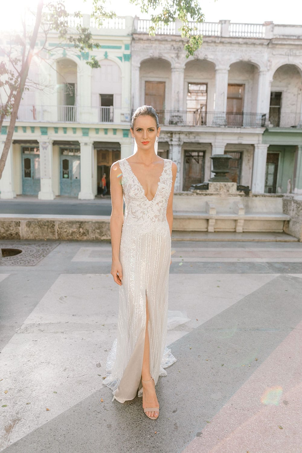 Model wearing Vinka Design Natalia Wedding Dress, a V-Neck Beaded Lace Wedding Gown face on with leg showing split in front of an old building with archways in Cuba