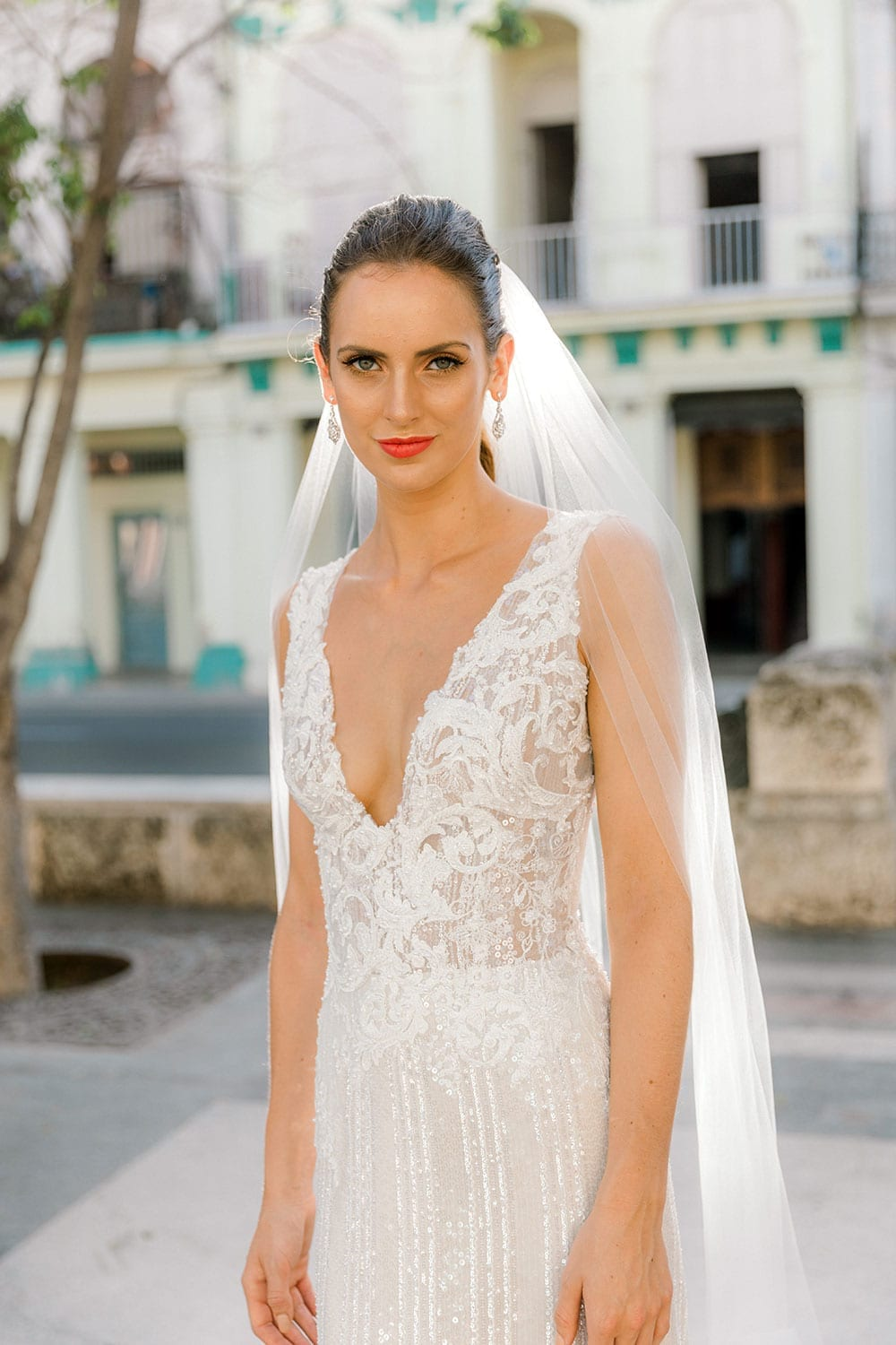 Model wearing Vinka Design Natalia Wedding Dress, a V-Neck Beaded Lace Wedding Gown close up showing v neck and complimented with veil in Cuba