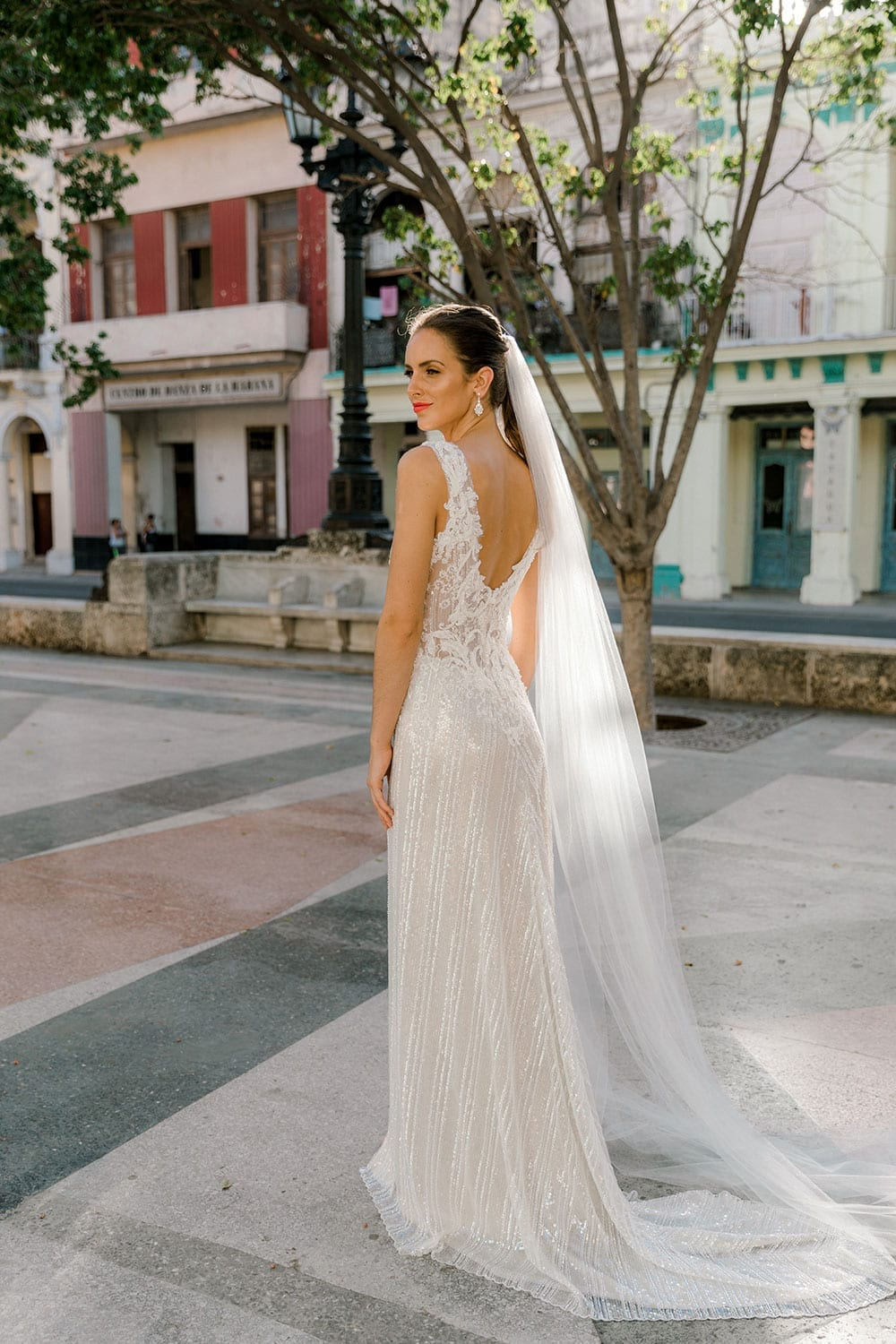 Model wearing Vinka Design Natalia Wedding Dress, a V-Neck Beaded Lace Wedding Gown showing dress from behind in a Cuban plaza