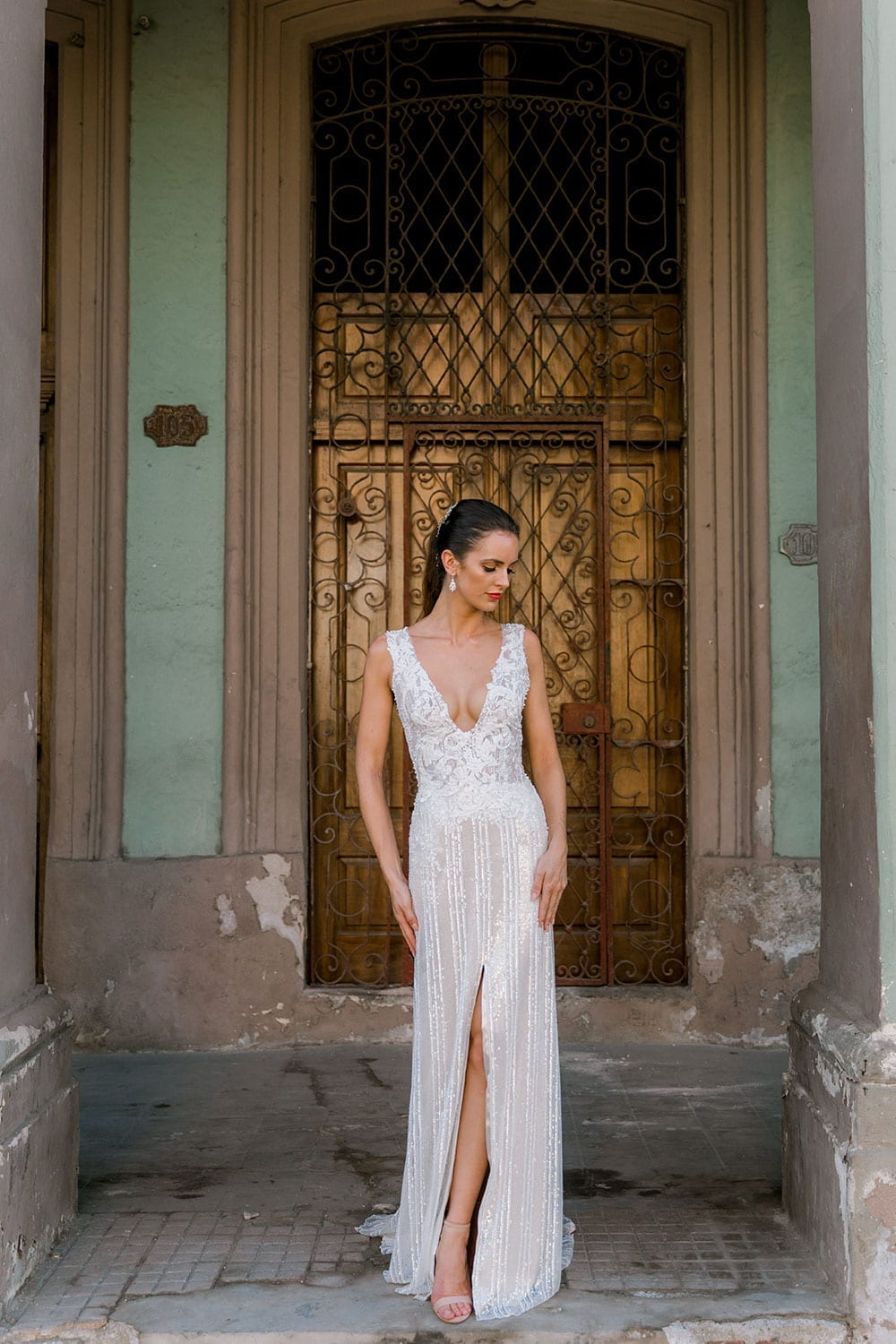 Model wearing Vinka Design Natalia Wedding Dress, a V-Neck Beaded Lace Wedding Gown in old doorway of Cuba