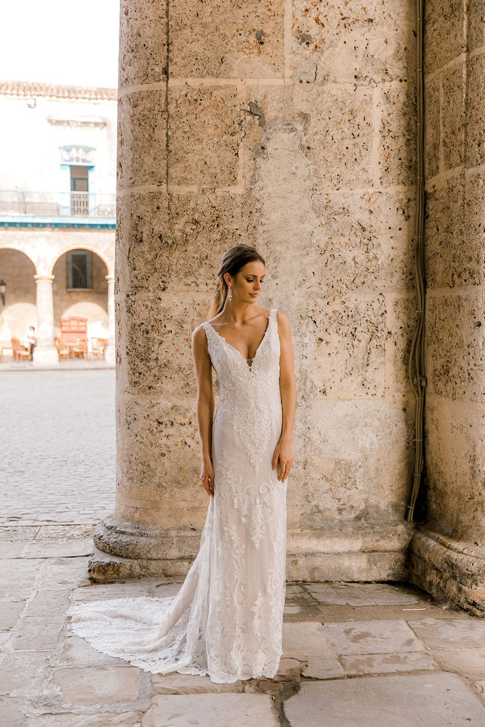 Model wearing Vinka Design Olivia Wedding Dress Low Back V-Neck Beaded Lace Wedding Gown in front of washed out stone column in Cuba square