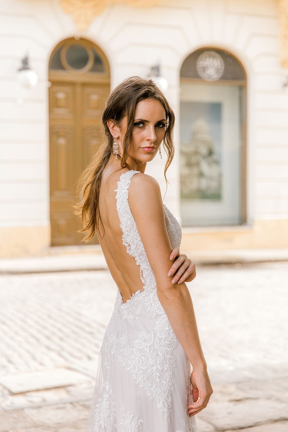 Model wearing Vinka Design Olivia Wedding Dress Low Back V-Neck Beaded Lace Wedding Gown between white pillars with old archways of Cuban buildings in background