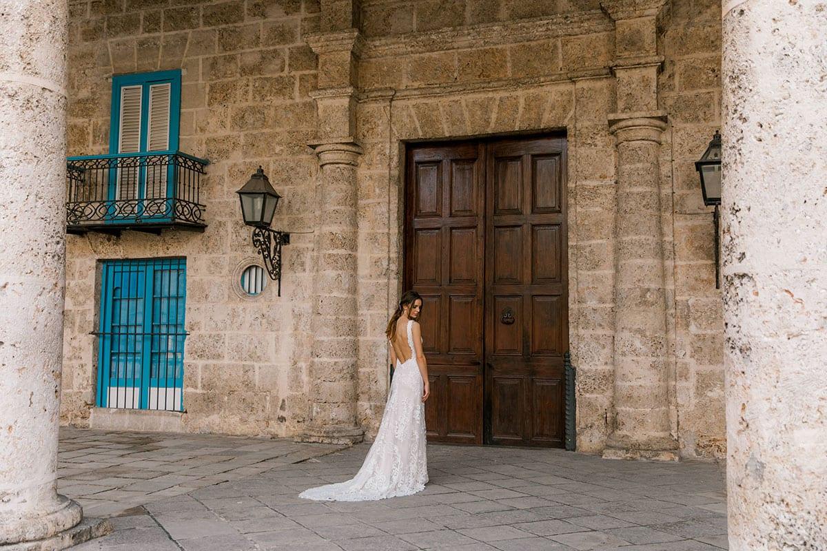 Model wearing Vinka Design Olivia Wedding Dress Low Back V-Neck Beaded Lace Wedding Gown in front of old brick building in Cuba