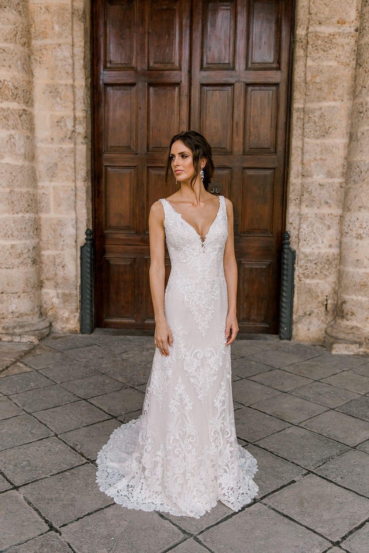 Model wearing Vinka Design Olivia Wedding Dress Low Back V-Neck Beaded Lace Wedding Gown in front of wooden door in Cuba