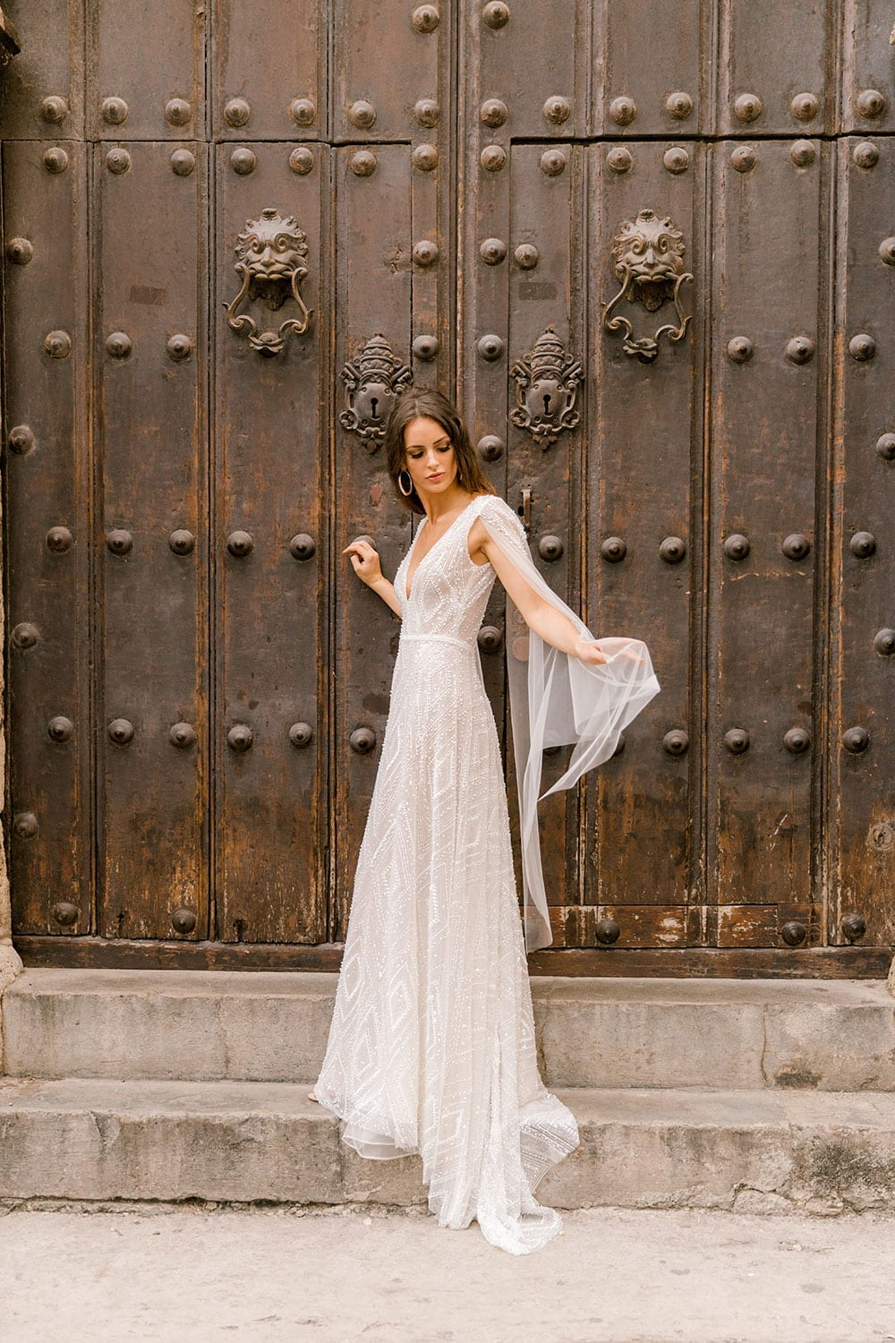 Model wearing Vinka Design Valentina Wedding dress with Deep V-Neck Beaded A-Line Gown taken in front of wooden door in Cuba with arms stretched to show tulle cape sleeve