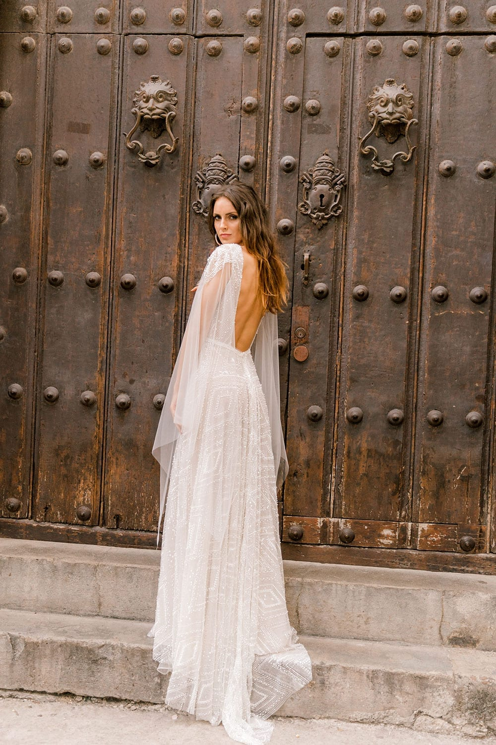 Model wearing Vinka Design Valentina Wedding dress with Deep V-Neck Beaded A-Line Gown facing wooden door to show back of dress in Cuba