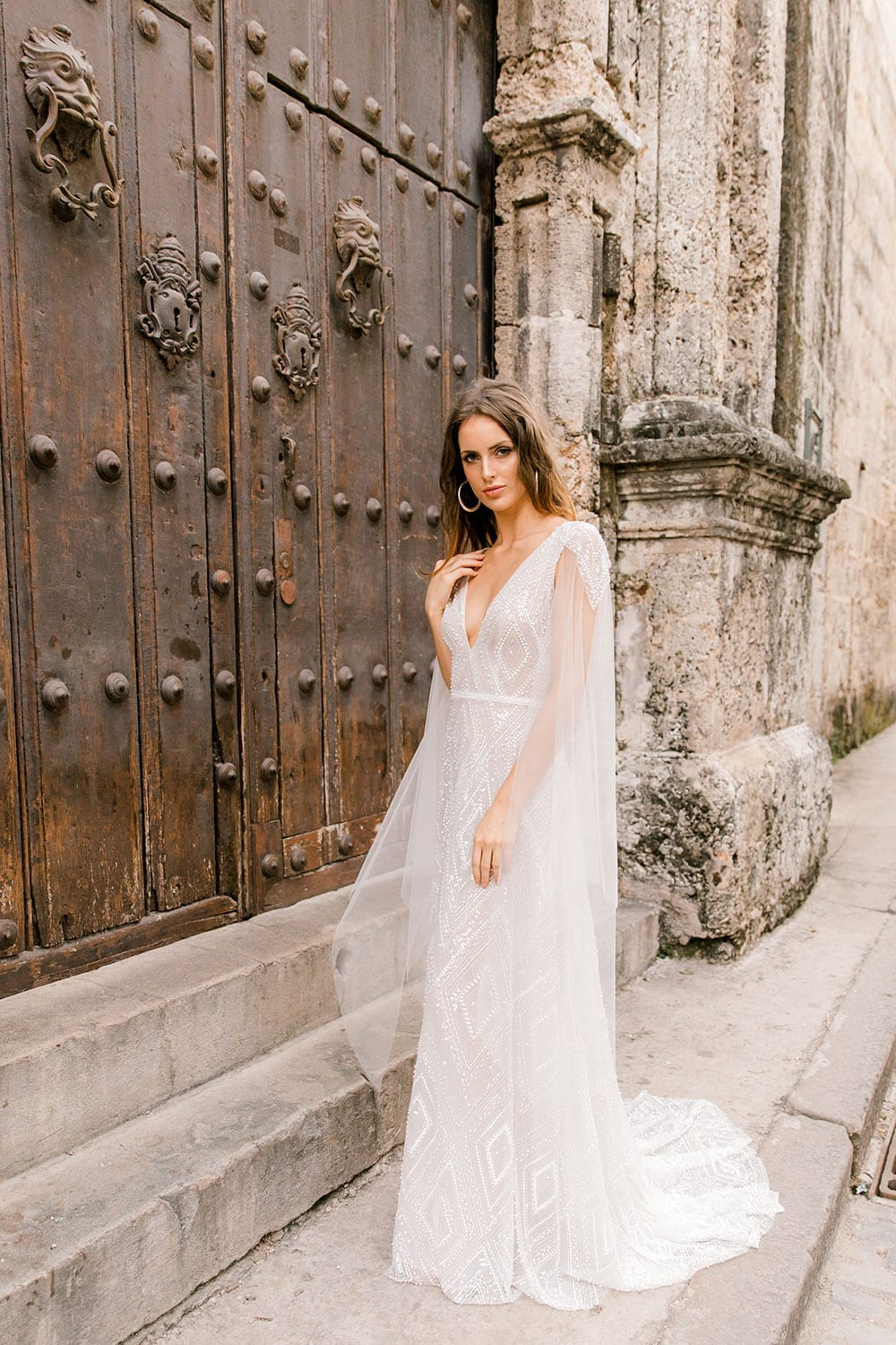 Model wearing Vinka Design Valentina Wedding dress with Deep V-Neck Beaded A-Line Gown in front of wooden door in streets of Cuba