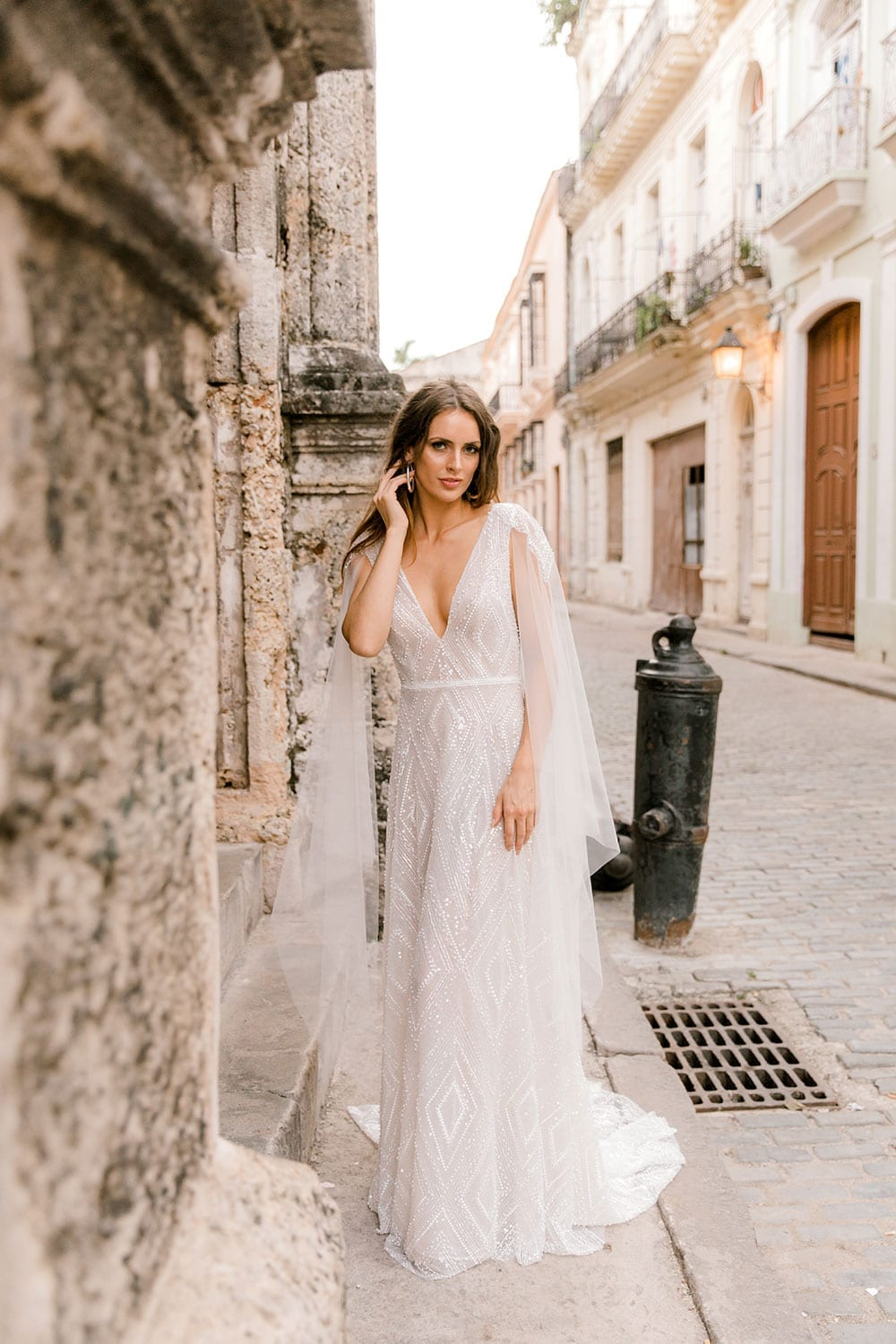 Model wearing Vinka Design Valentina Wedding dress with Deep V-Neck Beaded A-Line Gown in streets of Cuba