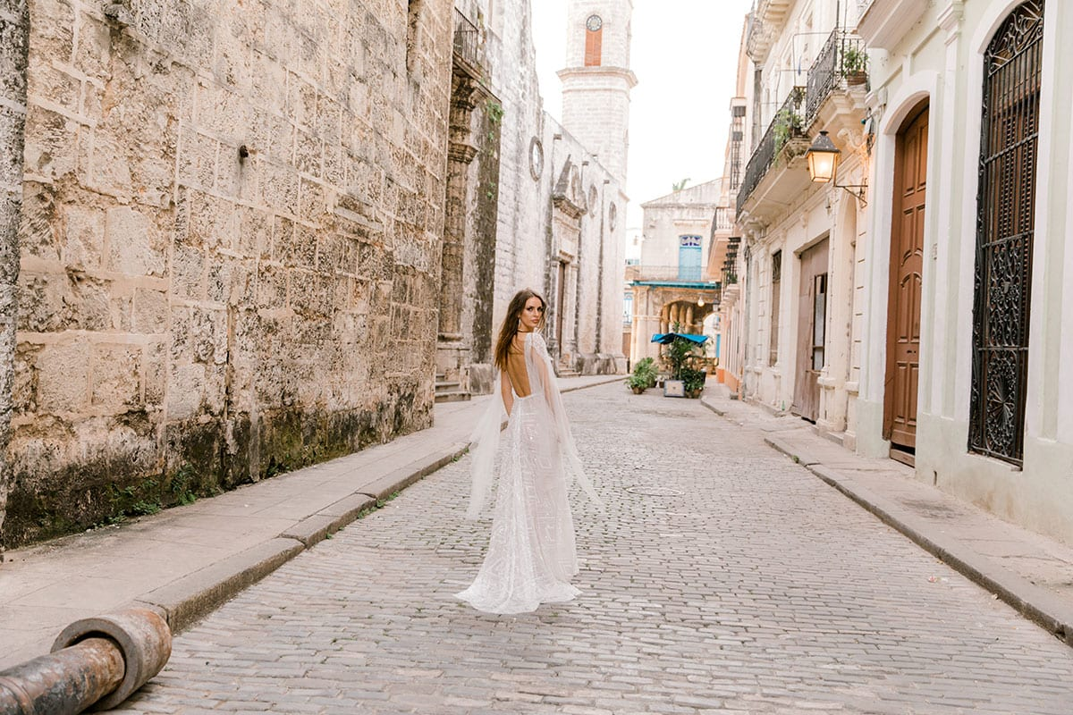Model wearing Vinka Design Valentina Wedding dress with Deep V-Neck Beaded A-Line Gown walking aay through cobble streets in Cuba