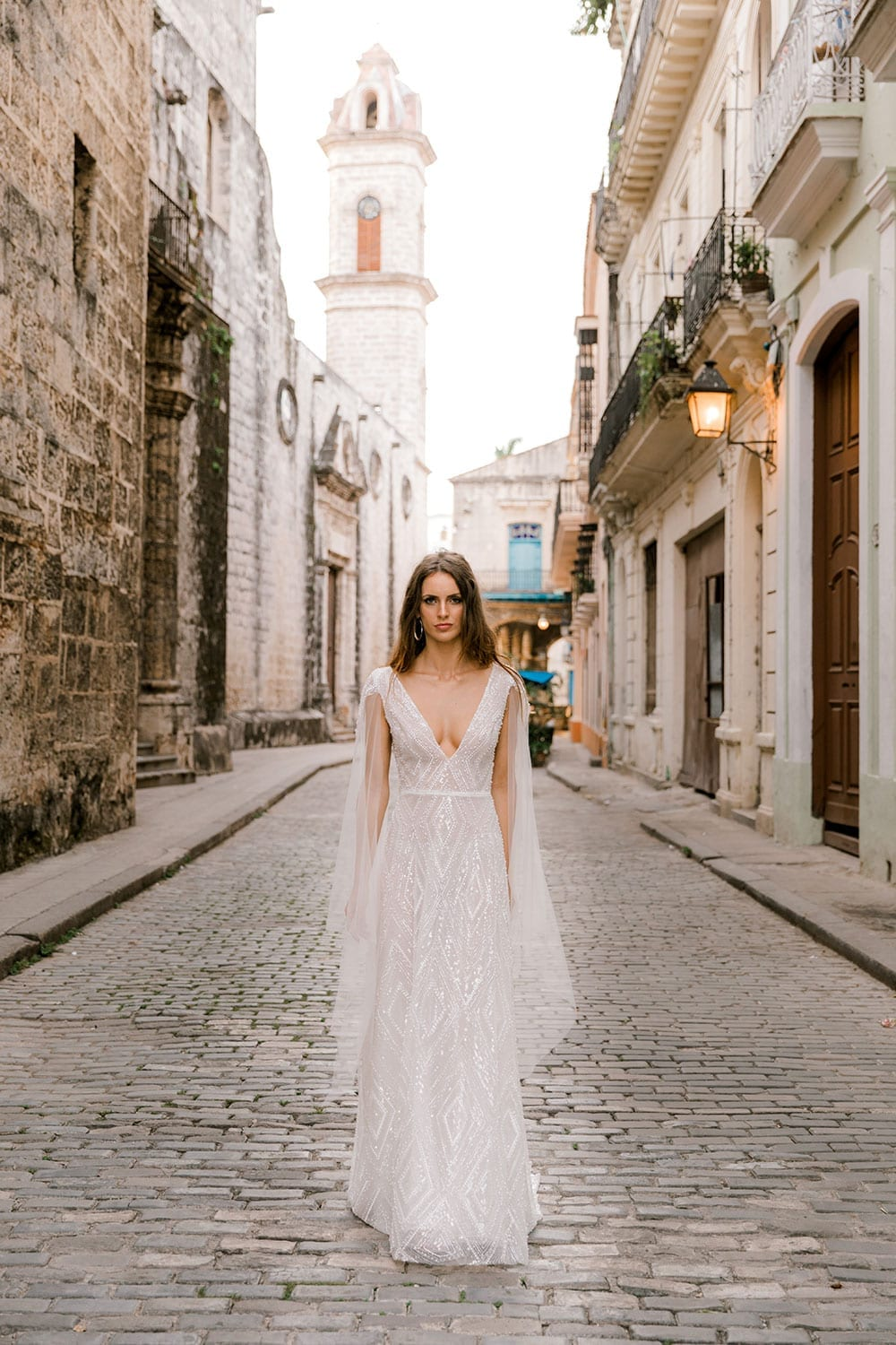 Model wearing Vinka Design Valentina Wedding dress with Deep V-Neck Beaded A-Line Gown on a cobbled Cuban street with high buildings either side