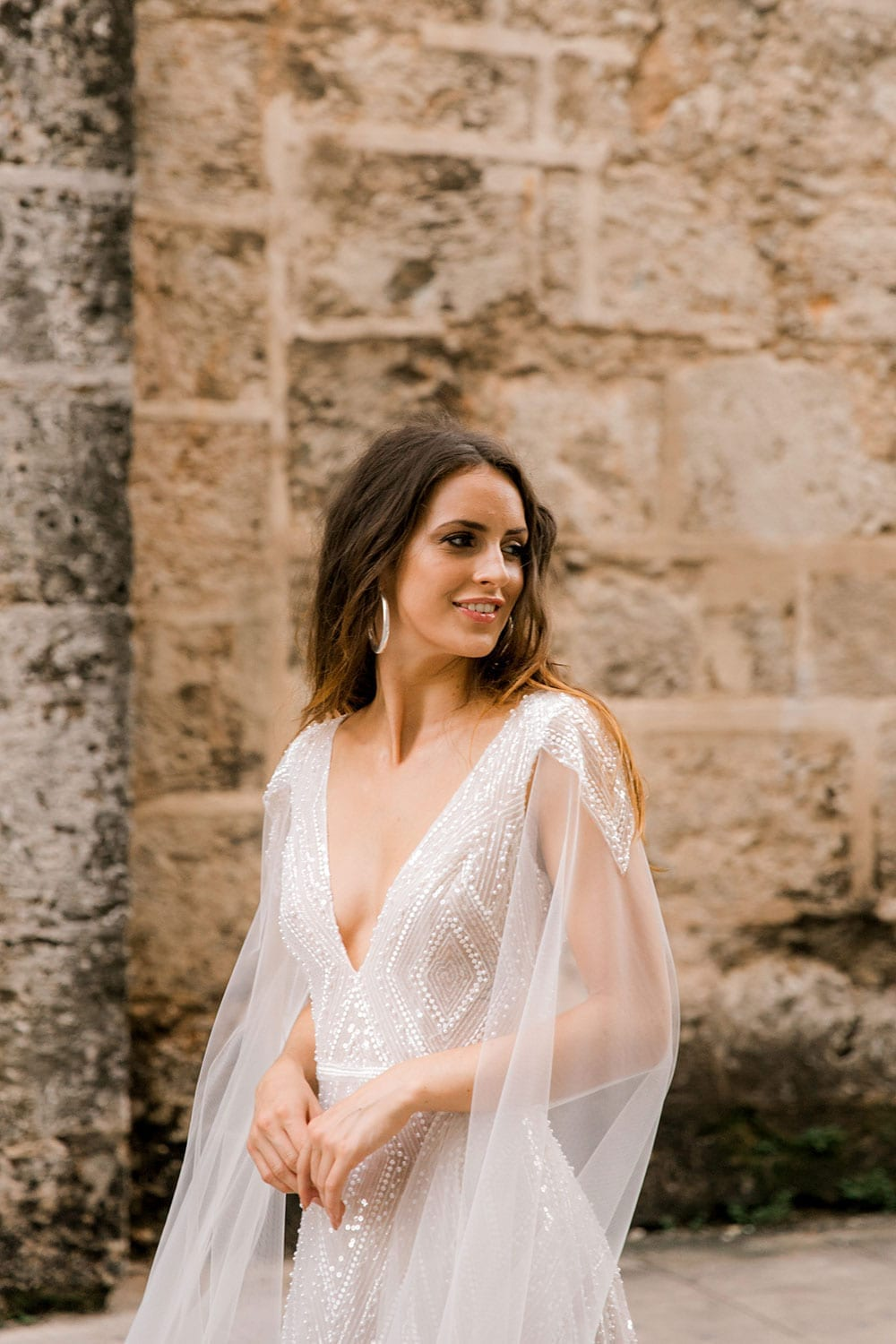 Model wearing Vinka Design Valentina Wedding dress with Deep V-Neck Beaded A-Line Gown with washed stone wall of Cuba behind