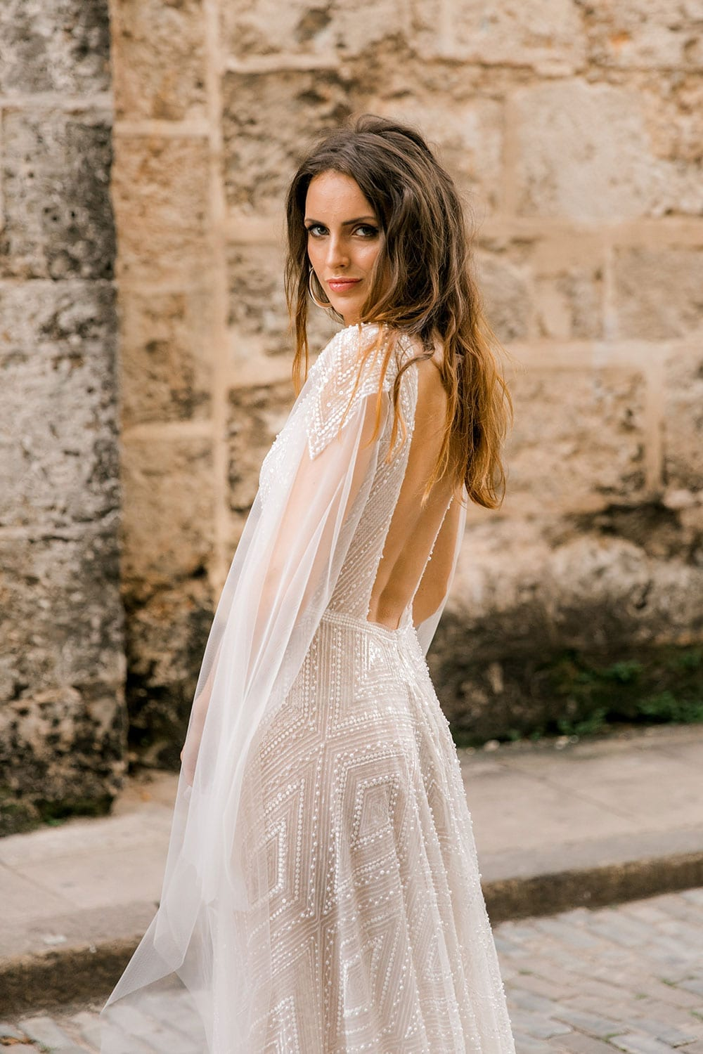 Model wearing Vinka Design Valentina Wedding dress with Deep V-Neck Beaded A-Line Gown side view showing deep back with washed stone wall of Cuba behind