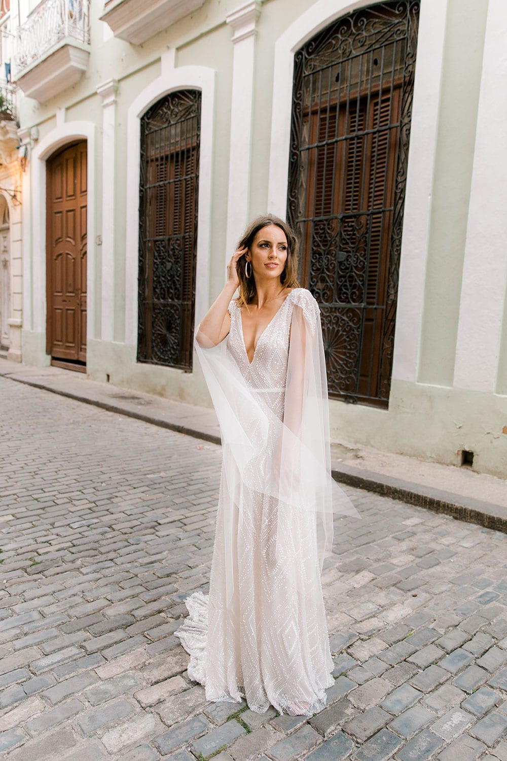 Model wearing Vinka Design Valentina Wedding dress with Deep V-Neck Beaded A-Line Gown on Cuba streets with wooden doors on building behind