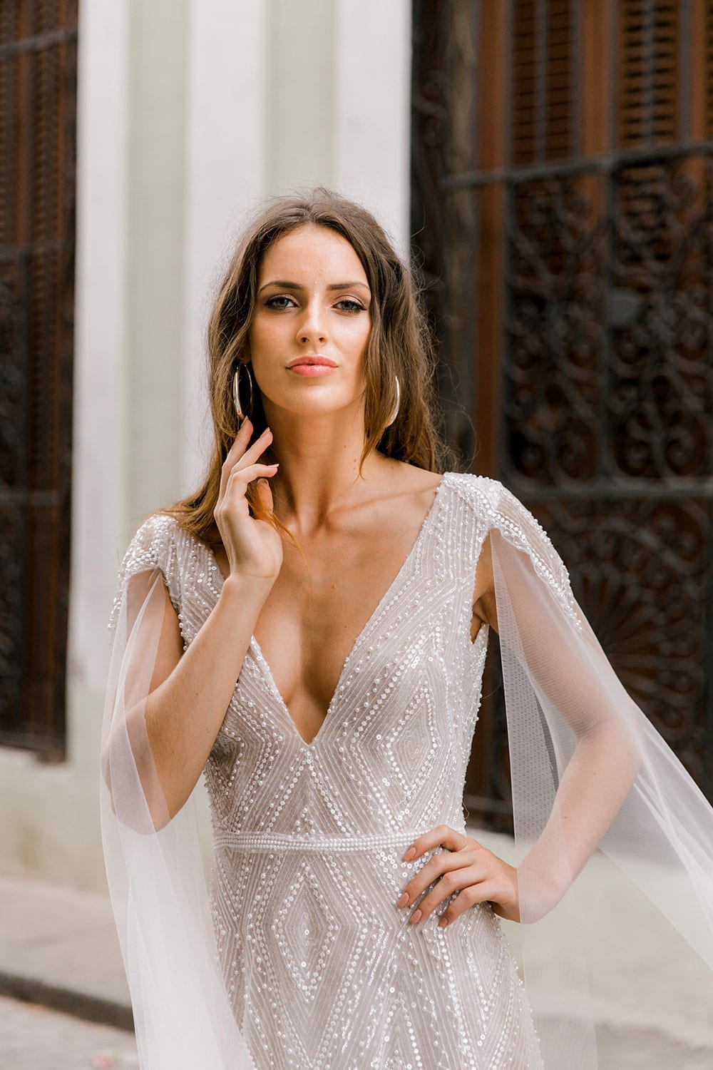 Model wearing Vinka Design Valentina Wedding dress with Deep V-Neck Beaded A-Line Gown close up showing deep V neckline tulle cape sleeve in Cuba streets