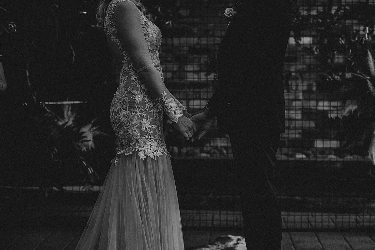 Real Weddings | Vinka Design | Real Brides Wearing Vinka Gowns | Rikki-Lee and Adam hold hands face to face lower half photo with dress detail highlighted in black and white